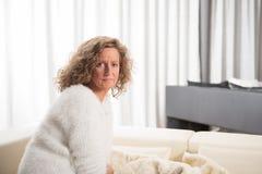 Mujer que se relaja en el sofá Fotografía de archivo