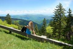 Mujer que se relaja en el top de la montaña Imagen de archivo