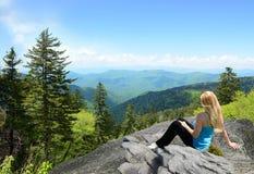 Mujer que se relaja en el top de la montaña Fotos de archivo