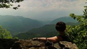 Mujer que se relaja en el top de la montaña metrajes