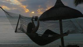 Mujer que se relaja en hamaca en la playa y que toma las fotos de la célula almacen de video