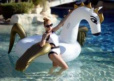 mujer que se relaja en hotel turístico de lujo de la piscina en el unicornio inflable grande que flota el flotador de Pegaso imágenes de archivo libres de regalías