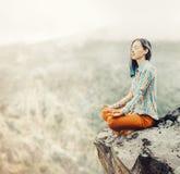 Mujer que se relaja en la actitud del loto en las montañas fotografía de archivo libre de regalías