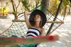Mujer que se relaja en la hamaca en la playa tropical en la sombra, día soleado caliente fotos de archivo