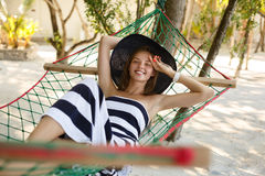 Mujer que se relaja en la hamaca en la playa tropical en la sombra, día soleado caliente La muchacha mira a la cámara con sonrisa imágenes de archivo libres de regalías
