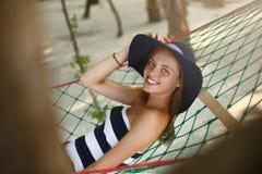 Mujer que se relaja en la hamaca en la playa tropical en la sombra, día soleado caliente La muchacha mira a la cámara con sonrisa imagen de archivo