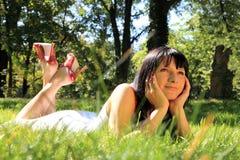Mujer que se relaja en la hierba Foto de archivo