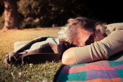 Mujer que se relaja en la manta en la puesta del sol Imagen de archivo libre de regalías
