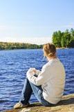Mujer que se relaja en la orilla del lago Fotos de archivo