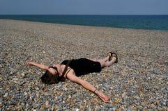 Mujer que se relaja en la playa Foto de archivo libre de regalías