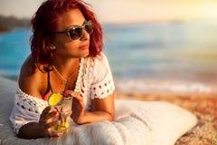 Mujer que se relaja en la playa de lujo con el cóctel concepto del ummer imagen de archivo libre de regalías