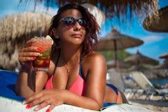 Mujer que se relaja en la playa de lujo con el cóctel concepto del ummer fotos de archivo libres de regalías