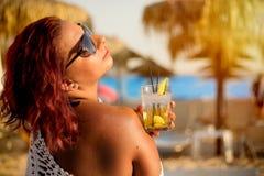 Mujer que se relaja en la playa de lujo con el cóctel concepto del ummer fotos de archivo