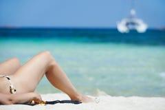 Mujer que se relaja en la playa del mar Imagen de archivo libre de regalías