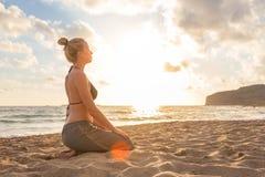 Mujer que se relaja en la playa del mar en la puesta del sol Imagen de archivo