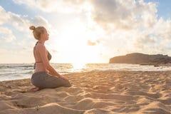 Mujer que se relaja en la playa del mar en la puesta del sol Foto de archivo libre de regalías