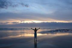 Mujer que se relaja en la playa en la salida del sol Fotografía de archivo