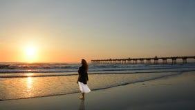 Mujer que se relaja en la playa en la salida del sol Fotografía de archivo libre de regalías