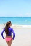 Mujer que se relaja en la playa en traje de baño de la protección del sol Imagen de archivo