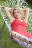 Mujer que se relaja en la sonrisa de la hamaca Imagen de archivo