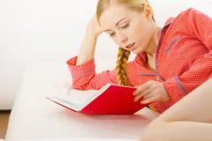 Mujer que se relaja en libro de lectura de la cama Fotografía de archivo libre de regalías