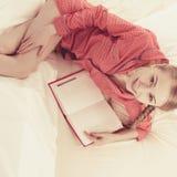 Mujer que se relaja en libro de lectura de la cama Foto de archivo libre de regalías
