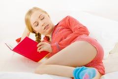Mujer que se relaja en libro de lectura de la cama Foto de archivo