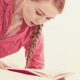 Mujer que se relaja en libro de lectura de la cama Fotos de archivo libres de regalías