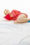 Mujer que se relaja en libro de lectura de la cama Imágenes de archivo libres de regalías