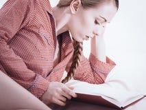 Mujer que se relaja en libro de lectura de la cama Fotografía de archivo
