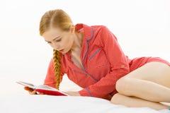Mujer que se relaja en libro de lectura de la cama Imagen de archivo libre de regalías