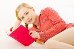 Mujer que se relaja en libro de lectura de la cama Imagen de archivo