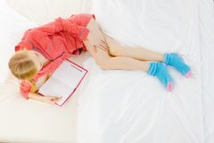 Mujer que se relaja en libro de lectura de la cama Imagenes de archivo