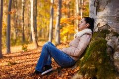 Mujer que se relaja en naturaleza mientras que estación del otoño Imágenes de archivo libres de regalías