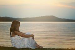 Mujer que se relaja en orilla del lago Foto de archivo libre de regalías