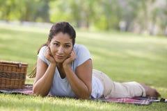 Mujer que se relaja en parque con comida campestre fotos de archivo