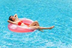 Mujer que se relaja en piscina Imagen de archivo libre de regalías