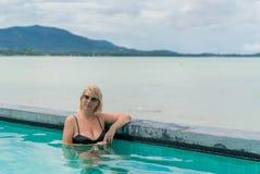 Mujer que se relaja en piscina Fotografía de archivo