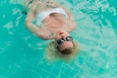 Mujer que se relaja en piscina Imagen de archivo