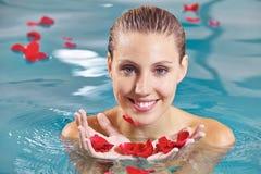 Mujer que se relaja en piscina con los pétalos de rosas Imagenes de archivo