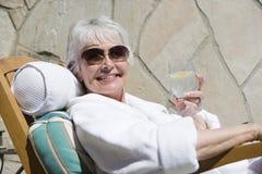Mujer que se relaja en sillón mientras que sostiene el vidrio de la bebida imagen de archivo
