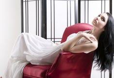 Mujer que se relaja en silla Imagenes de archivo
