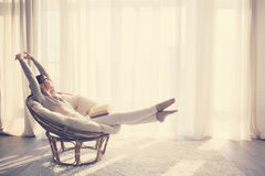 Mujer que se relaja en silla Imagen de archivo libre de regalías