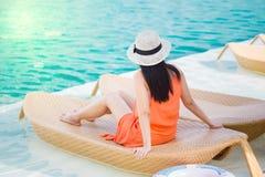 Mujer que se relaja en silla de cubierta por la piscina Imagen de archivo