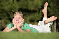 Mujer que se relaja en un césped Imagen de archivo libre de regalías