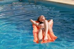 Mujer que se relaja en un colchón inflable en piscina imagenes de archivo