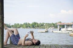 Mujer que se relaja en una lectura del embarcadero Foto de archivo