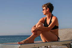 Mujer que se relaja en una playa Imagen de archivo libre de regalías
