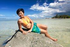 Mujer que se relaja en una roca por una playa tropical imagen de archivo libre de regalías
