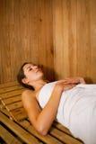 Mujer que se relaja en una sauna Imagen de archivo